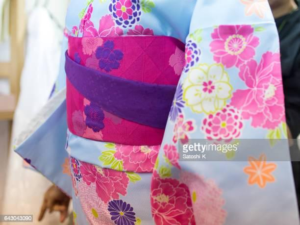 Young woman tying sash on Kimono