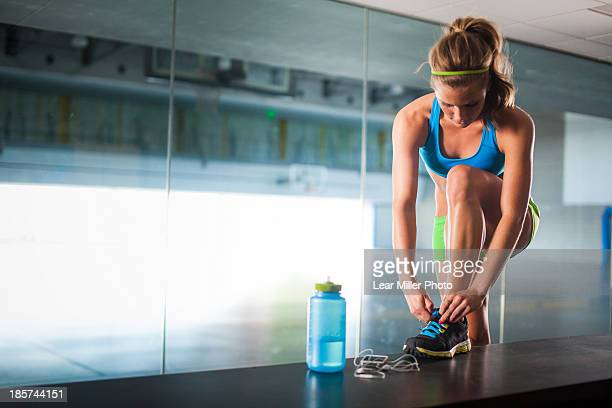 Young woman tying shoelace in gym