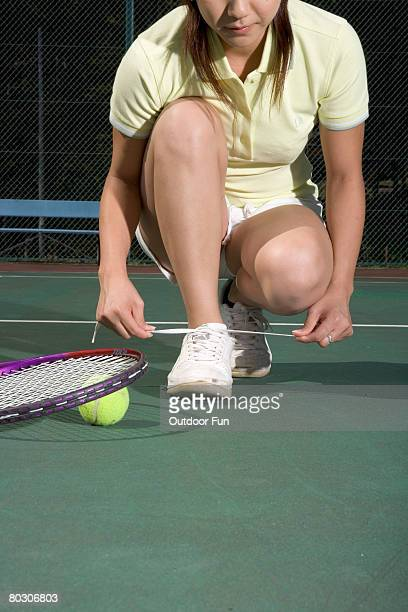 Young woman tying shoelace on tennis court