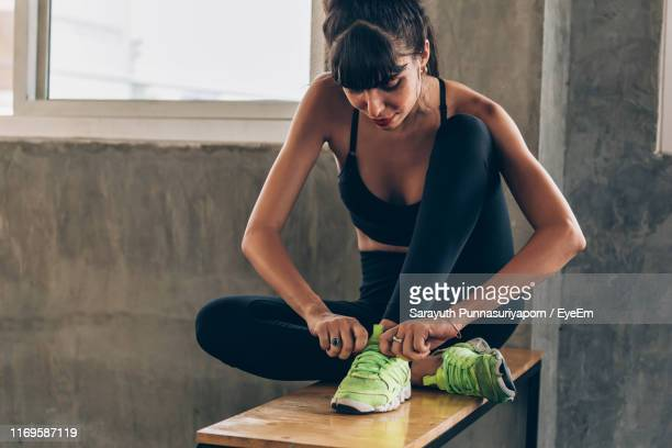 young woman tying shoelace while sitting on table - shoelace stock pictures, royalty-free photos & images