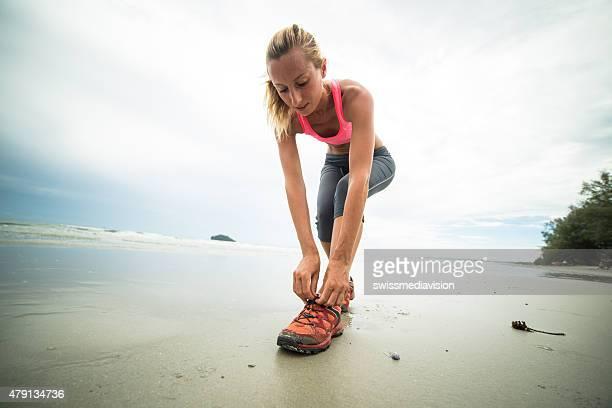 Jeune femme attacher des chaussures de sport sur la plage