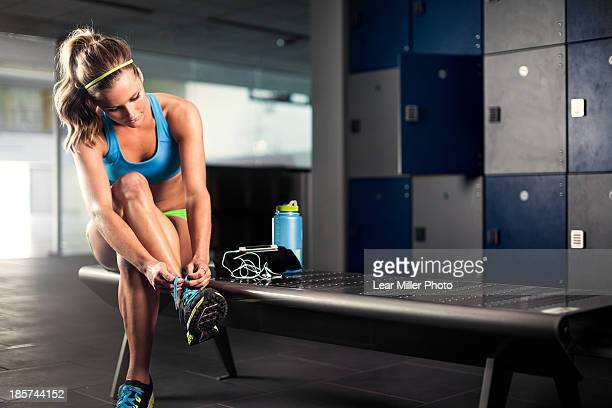 young woman tying trainer lace in gym - locker room stock pictures, royalty-free photos & images