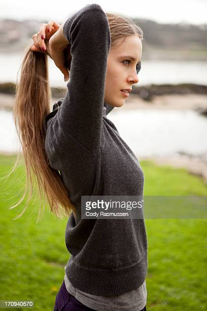 Young woman tying up hair