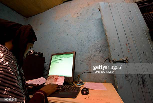 A young woman types an article into a computer at a cyber cafe on June 20 2012 at the Kibera slum in Nairobi The Kenya government in a bid to reduce...
