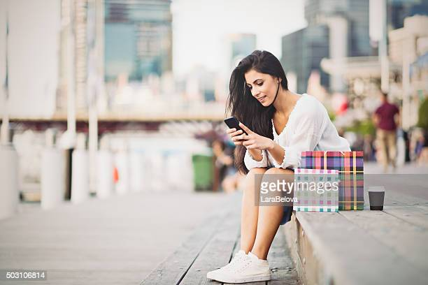 young woman typing a message on smart phone - darling harbour stock pictures, royalty-free photos & images