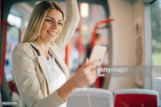 Young Woman Typing On Her Smart Phone In Public Transportation.