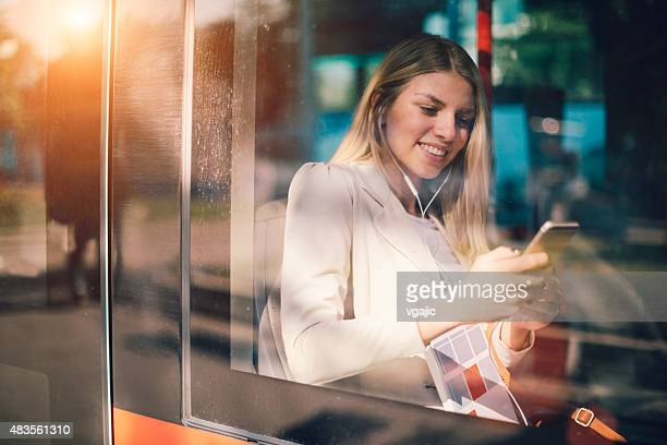 young woman typing on her smart phone in public transportation. - tram stockfoto's en -beelden