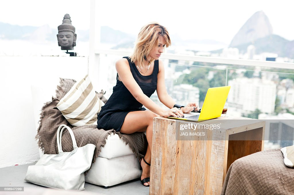 Young woman typing on laptop on rooftop terrace, Rio De Janeiro, Brazil : Stock-Foto