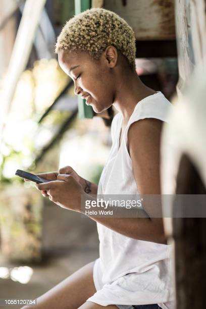 young woman typing on smart phone, side view - bleached hair stock photos and pictures