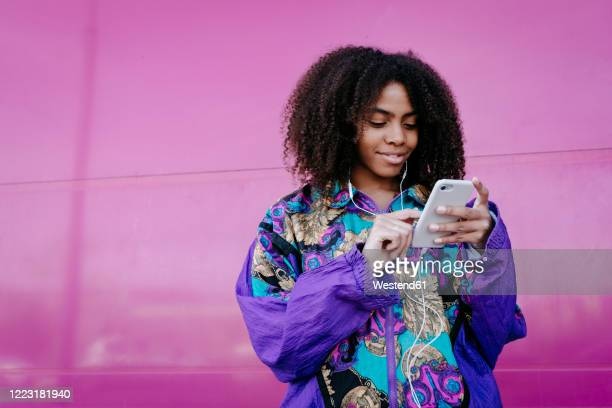 young woman typing on smartphone and listening to music - black hair stock pictures, royalty-free photos & images