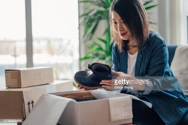 young woman unboxing online purchases in living room - receiving stock pictures, royalty-free photos & images
