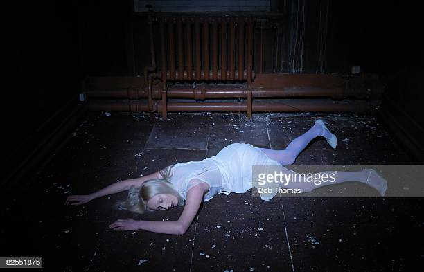young woman lying on floor - dead female bodies stockfoto's en -beelden