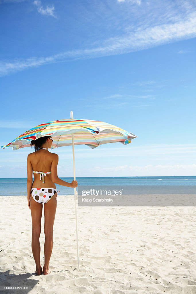 Young woman under beach umbrella, rear view : Stock Photo