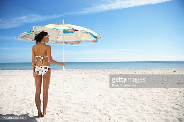 Young woman under beach umbrella, rear view