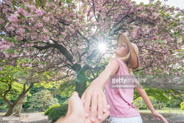 Young woman under sakura tree holding man's hand