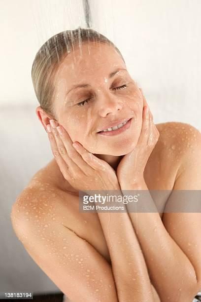 young woman under shower - frau unter dusche stock-fotos und bilder