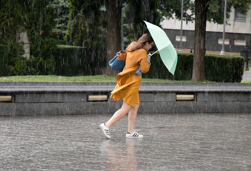 Young woman under umbrella during sudden spring shower 983517772