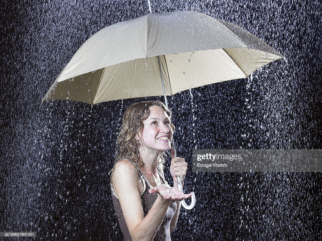 Young Woman Under Umbrella In Rain Stock Photo - Getty Images