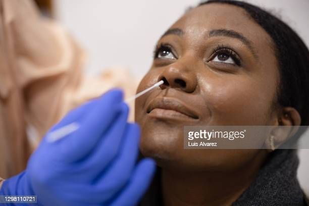 young woman undergoing a coronavirus test - covid-19 stock pictures, royalty-free photos & images