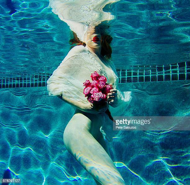 Young woman underwater, wearing thin white shirt and holding flowers