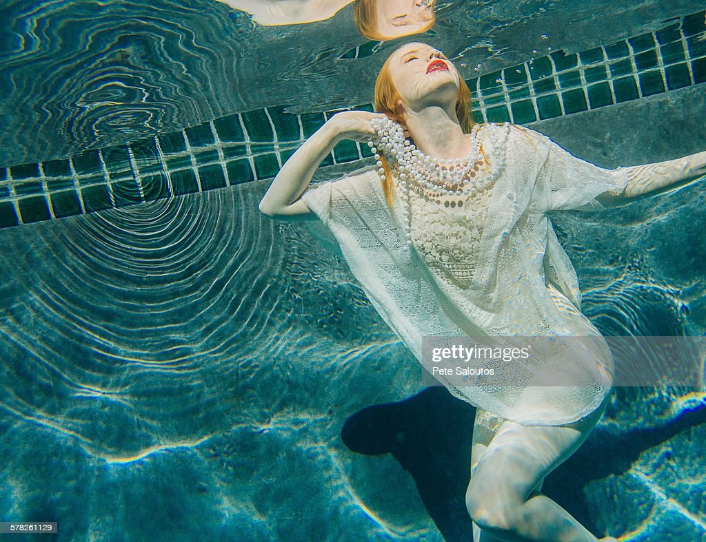 Young Woman Underwater Wearing Thin White Shirt High-Res