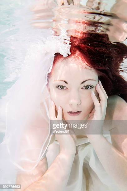 Young woman underwater, wedding dress and red hair