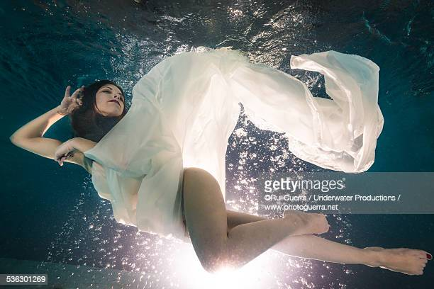 Young woman underwater with white transparent dres