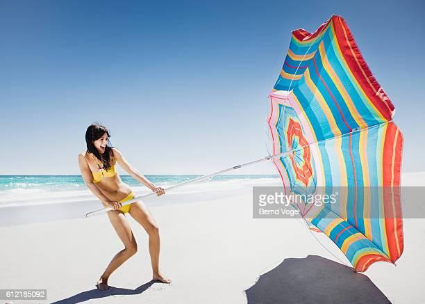Young woman unfurling umbrella on windy beach