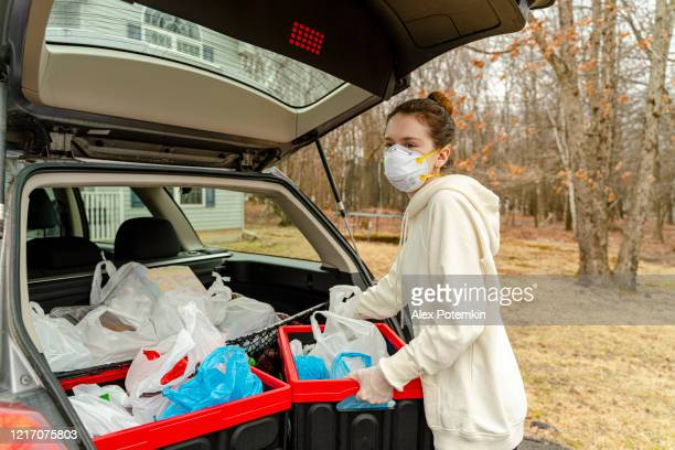 young woman unloading plastic reusable bins filled with groceries from the car's trunk to be delivered. - n95 face mask stock pictures, royalty-free photos & images