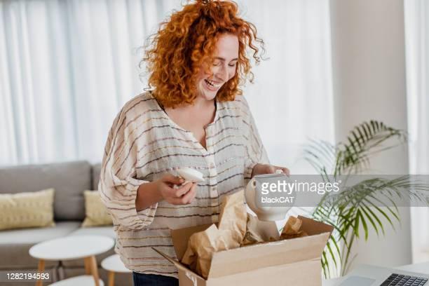 jovem desempacotar o pacote que ela pediu online - receber - fotografias e filmes do acervo