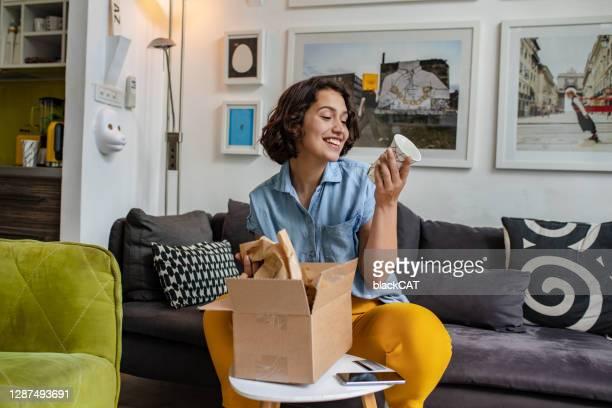 jonge vrouw pakt het pakket dat ze online besteld - ontvangen stockfoto's en -beelden