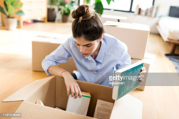 young woman unpacking cardboard box in new apartment - unpacking stock pictures, royalty-free photos & images