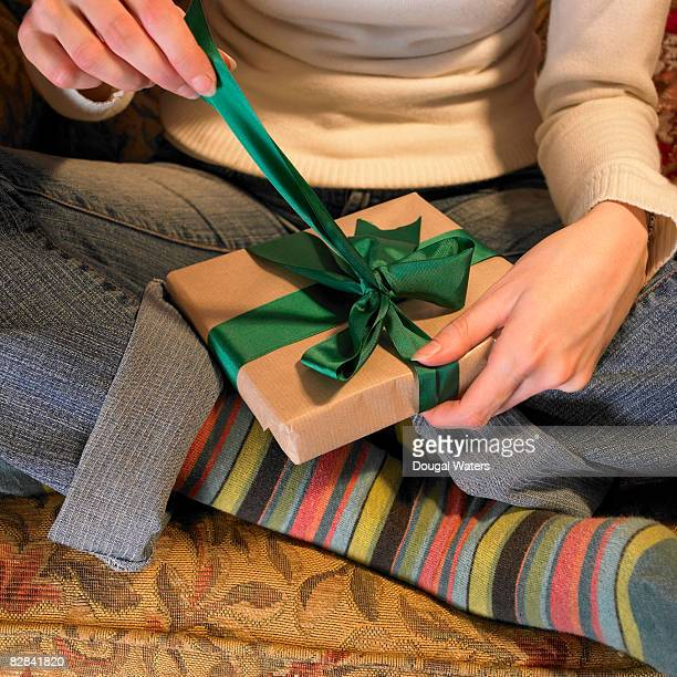 Young woman unwrapping christmas present.