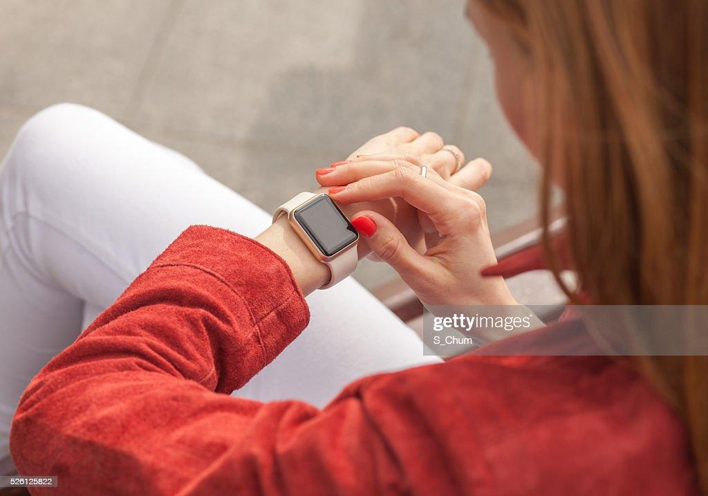 Junge Frau mit Smart Uhr mit leeren Bildschirm im Freien : Stock-Foto