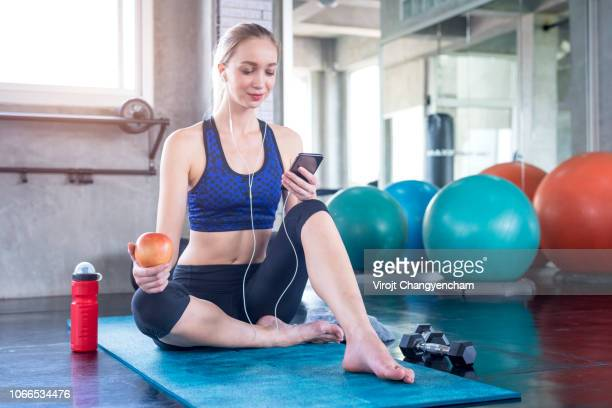 young woman use smartphone and holding red apple after workout in the gym - nutriologo fotografías e imágenes de stock