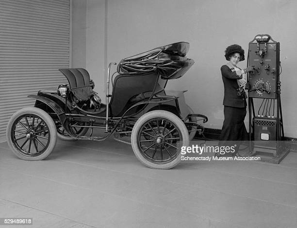 A young woman uses a handcranked battery charger to charge her electric Columbia Mark 68 Victoria automobile The Pope Manufacturing Company of...