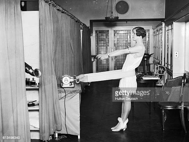 A young woman uses a mechanical device to keep her hips slim