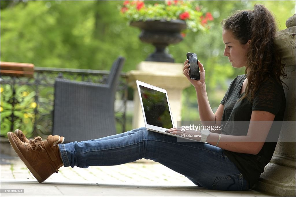 A young woman uses a mobile phone and laptop on June 25, 2013 in Brussels, Belgium.