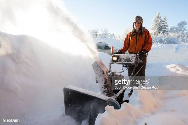 a young woman uses a snowblower in the deep snow - home run ストックフォトと画像