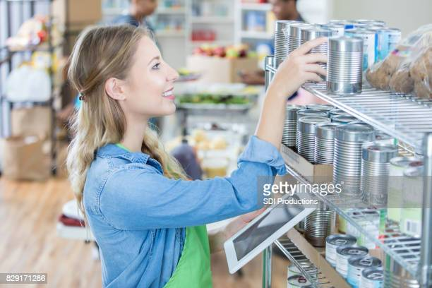 young woman uses digital tablet in food bank - non profit organization stock pictures, royalty-free photos & images