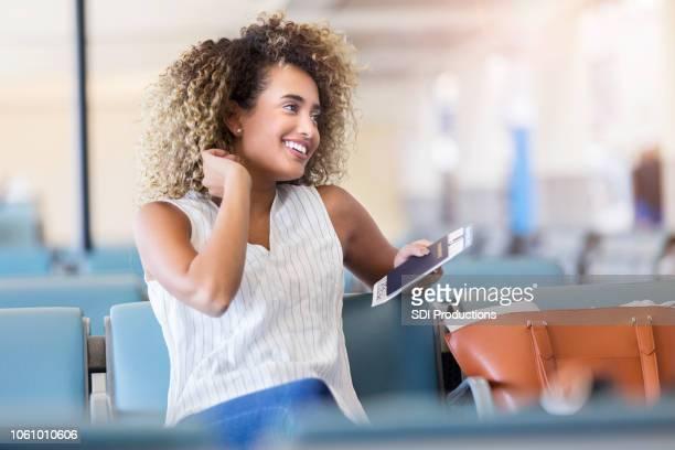 giovane donna usa il suo cellulare mentre aspetta il suo volo - afro americano foto e immagini stock