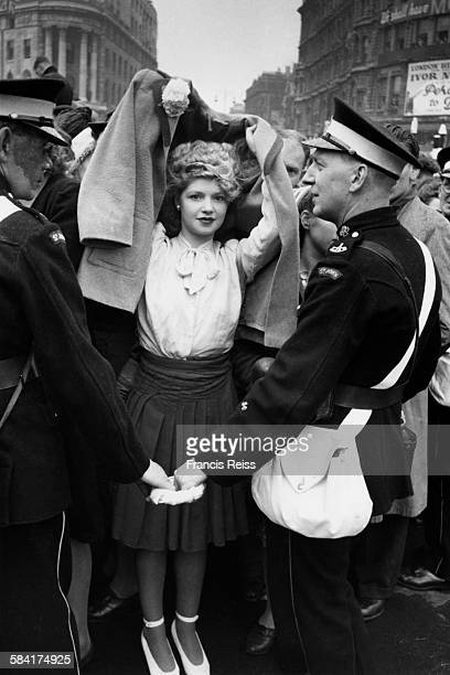 A young woman uses her coat to protect her coiffured hair from the rain during the Victory Day parades in London 8th June 1946 Original Publication...