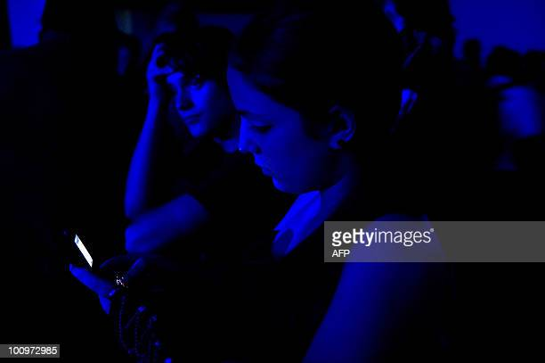 A young woman uses her mobile phone during a pop music concert in Caracas May 25 2010 AFP PHOTO / Miguel GUTIERREZ