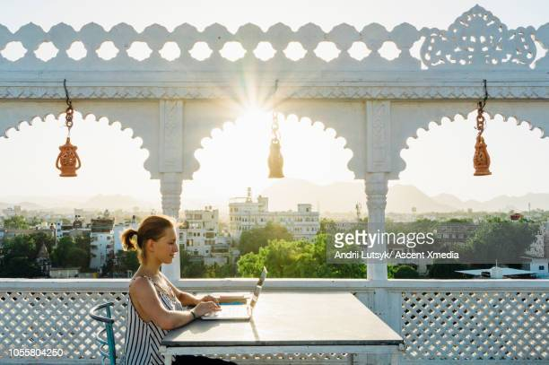 young woman uses laptop computer in outside courtyard - udaipur stock pictures, royalty-free photos & images