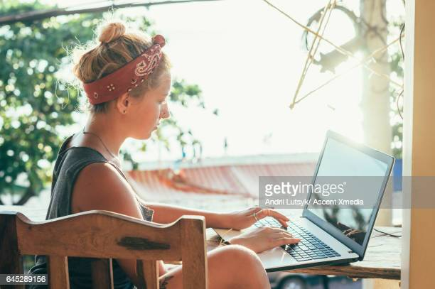 Young woman uses laptop computer in tropical setting