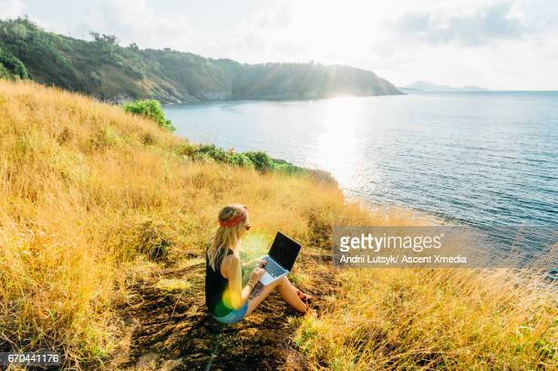 Young woman uses laptop computer, on hillside above sea