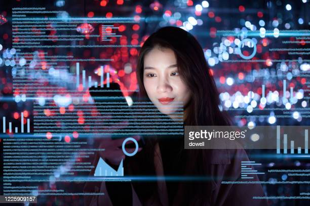 young woman uses mobile phone on virtual visual screen at night - big data screen stock pictures, royalty-free photos & images
