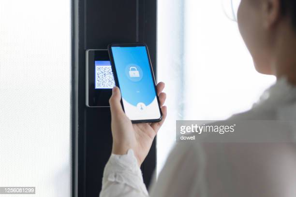 young woman uses mobile phone with qr scanner on wall - strichkodeleser stock-fotos und bilder