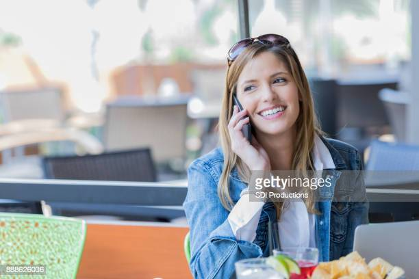 young woman uses phone while at a restaurant - texas independence day stock pictures, royalty-free photos & images