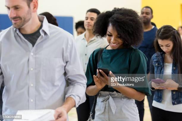 junge frau nutzt telefon, während sie auf die abstimmung wartet - demokratie stock-fotos und bilder